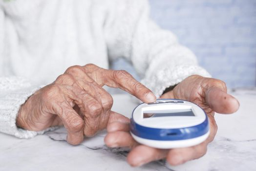 Senior women diabetic measure glucose level at home