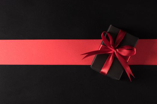 Gift box wrapped black paper and black bow ribbon present