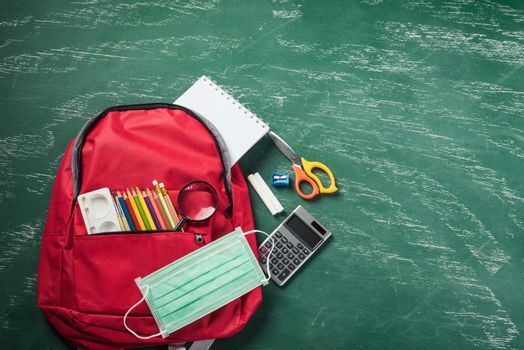 red school bag backpack at a green chalkboard with face mask protection and stationery