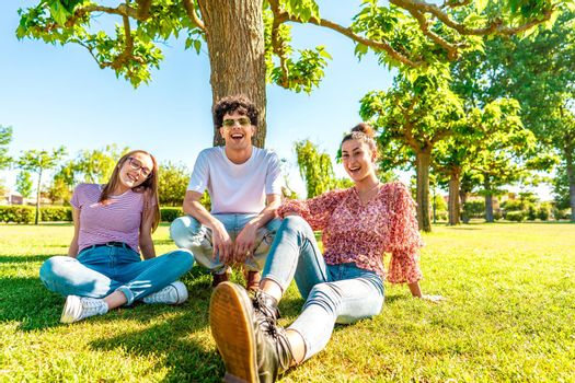 Three young diverse friends resting on green park field smiling looking at camera for a portrait. Gen z students spending time in nature to breaking city life routine. Friendship makes no difference