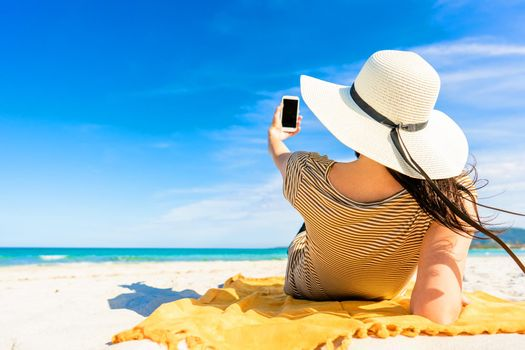 Back shot of fashionable young unrecognizable woman in large white hat lying on sand of tropical beach taking selfie with smartphone sharing vacations on social network. Bright vivid color photograph