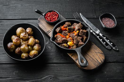 Beef meat and vegetables stew, in cast iron frying pan, on black wooden background