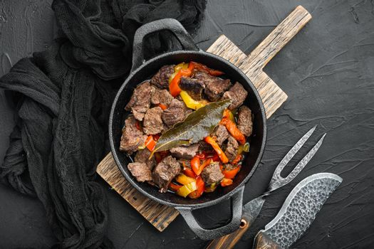 Bangin beef stew, in cast iron frying pan, on black stone background, top view flat lay, with copy space for text