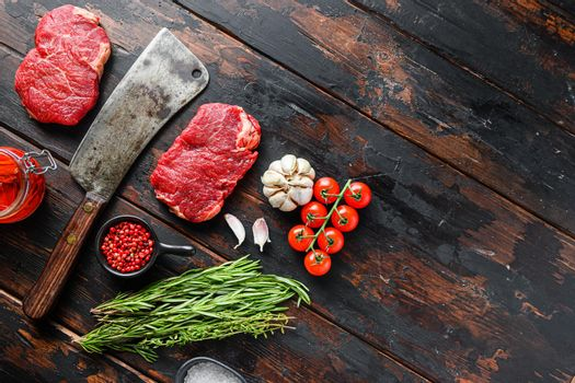 Rump steak, raw marbled beef steak, with old butcher knife cleaver, and seasonings On dark wooden rustic table, top view with space for text.