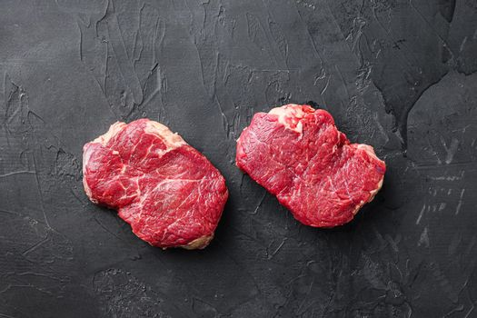 Set of raw rump steaks over black textured background, top view.