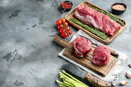 Prime Raw Fillet Mignon tenderloin steaks, on wooden cutting board, on gray stone background, with copy space for text