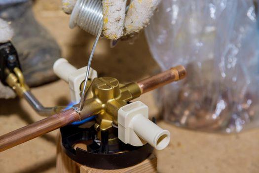 Blue flame torch soldering a brass diverter for shower bathtub