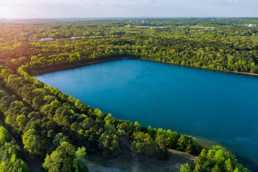 Aerial panorama view on the green forest between turquoise color lake