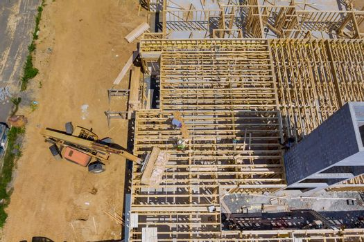 Aerial view of apartment framing of a new house under construction with forklift stacker wooden boards the construction trash dumpsters