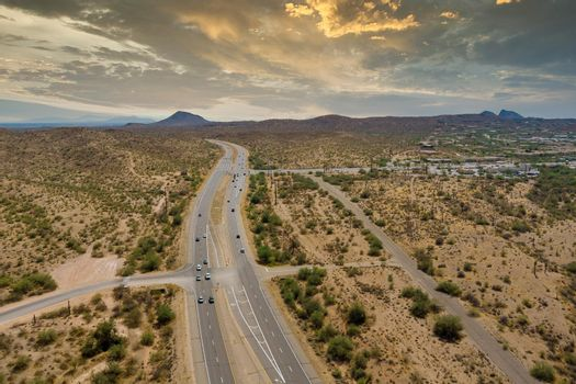 Aerial view highway across the arid desert Arizona mountains adventure traveling desert road near Fountain Hills small town residential district