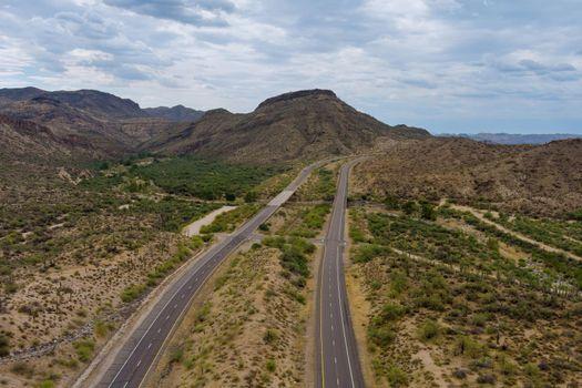 Aerial view adventure traveling desert road of the asphalt highway across the arid desert Arizona mountains