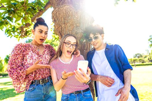Three diverse students making surprised faces spreading mouth and eyes pointing and looking smartphone spending time in nature of city park. power of new wifi technology addicting all ages people