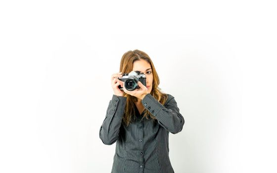 Beautiful young woman holding retro camera pointing subject and rotates focus ring on lens. Vintage versus new photography technologies at modern times. Large copy space for online photo courses adv
