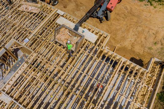 Wood building frame on new residential construction home framing home boom truck forklift in the new home