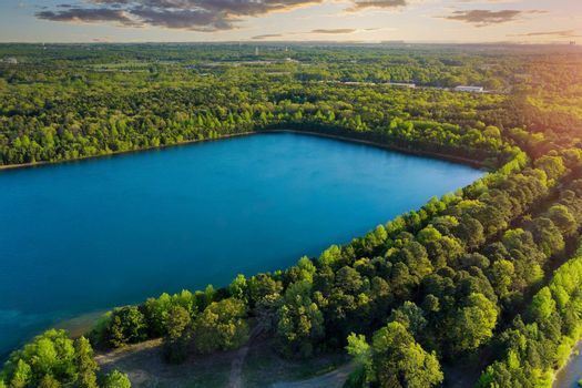 Landscape panorama, blue water in a forest lake with trees