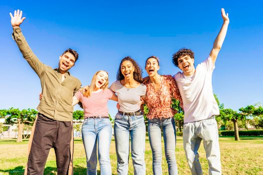 Multiracial group of young friends posing with raised open arms looking at camera embracing to each other in nature of city park. Happy diverse people having fun together enjoying life and success
