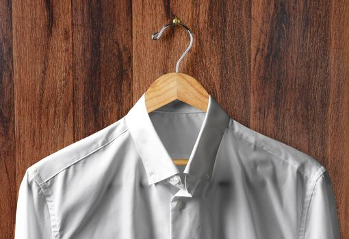 Closeup of a White Dress Shirt on a wooden hanger hanging from a hook on a dark wood paneled wall.