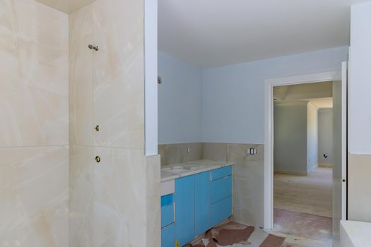 Bathroom with sink and walls tiled shower curtain.