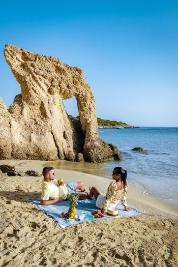 The tropical beach of Voulisma beach, Istron, Crete, Greece Europe, couple men and woman mid-age on the beach during a vacation in the summer of Europe, Asian woman with European man