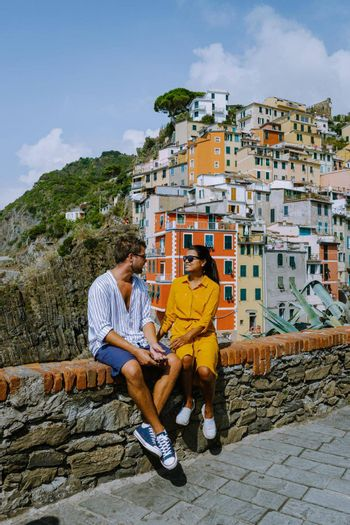 View of Riomaggiore Cinque Terre sequence of hill cities. Wonderful view of Liguria, Italy, Europe. seascape of the Mediterranean sea. Traveling concept background. couple man and women on vacation Riomaggiore Cique Terre Italy