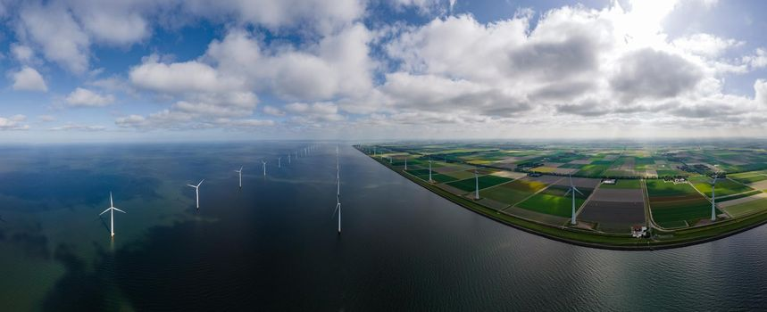 offshore windmill park with clouds and a blue sky, windmill park in the ocean aerial view with wind turbine Flevoland Netherlands Ijsselmeer. Green energy