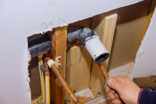 Maintenance plumber service home bathroom in repair of plastic polypropylene water pipes in hole wall