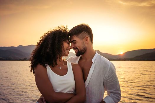 Romance scene of multiracial stylish couple in love looking in eyes head to head at sunset with sun setting among mountain in background. Handsome guy in white shirt flirting with Hispanic girlfriend