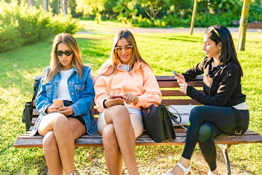 Three young woman best friends sitting on a city park bench at sunset or dawn using telephone to messaging with other friends. New relationships in modern times. Girls having fun with smartphone