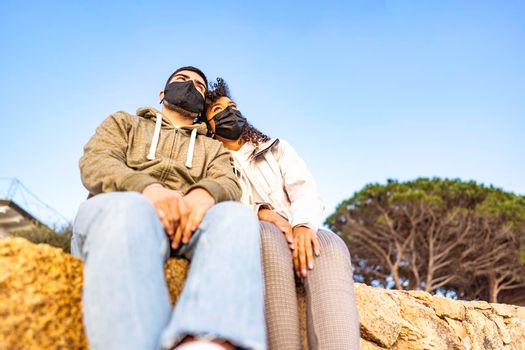 Young multiracial couple in love sitting on a wall wearing black safe protective face mask head to head looking at horizon at sunset. Pandemic global issue disturbing normal life and people future