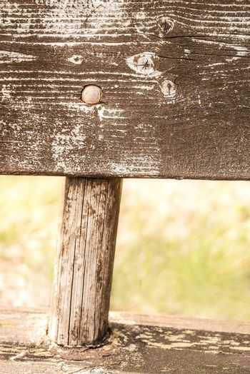 Closeup detail of a weathered and natural faded rural wooden bench neglected in the countryside, with a rustic and vintage style