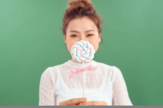 young attractive woman hiding mouth behind colored lollipop