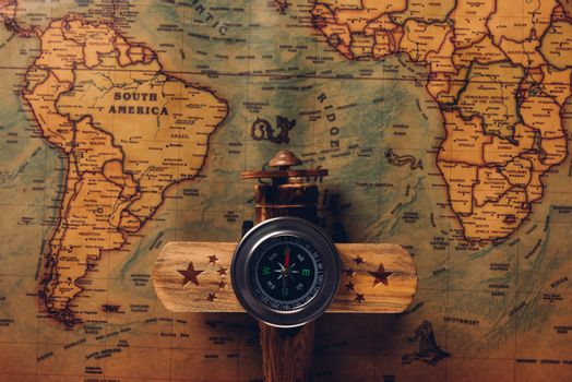 Old compass discovery and wooden plane on vintage paper antique world map
