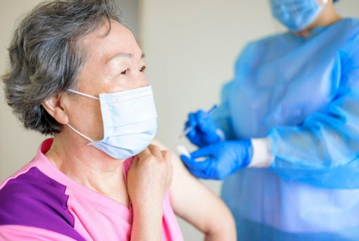 Doctor doing vaccine injection to senior woman