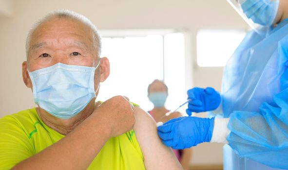 Doctor doing vaccine injection to senior man