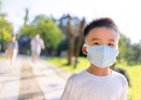 Happy little boy wearing medical mask and walking with parent in the park