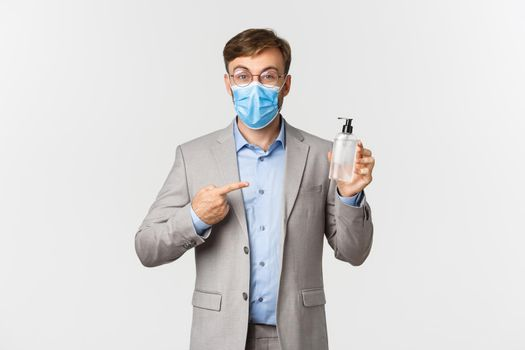 Concept of work, covid-19 and social distancing. Image of male employer in gray suit and medical mask, pointing at hand sanitizer or antiseptic, standing over white background