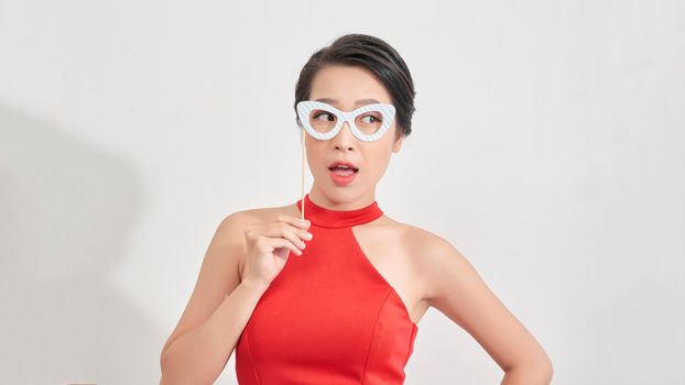Portrait of good-looking stylish young girl attend party with face mask of glasses on stick, smiling see no proble, standing white background