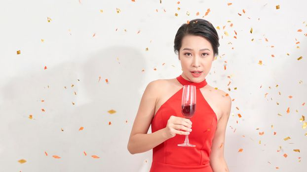 Indoor portrait of good-looking asian woman drinks champagne under confetti.