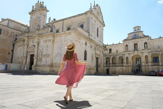 Beautiful young woman walking in the Cathedral Square of the Baroque City of Lecce, Salento, Italy
