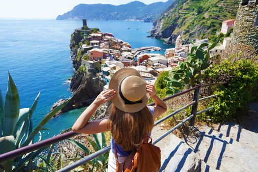 Tourism in the Cinque Terre of Italy. Young female backpacker walks the Azure Trail and looking at Vernazza village, Italy.