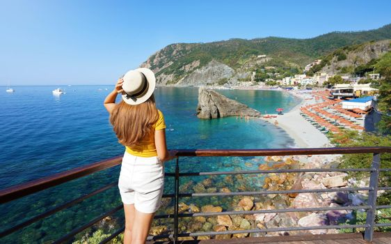 Beautiful young woman with hat on terrace looking at panoramic of Monterosso al Mare village on Cinque Terre, Italy