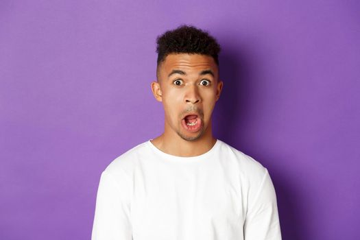 Close-up of impressed african-american man, drop jaw and stare at something amazed, standing over purple background