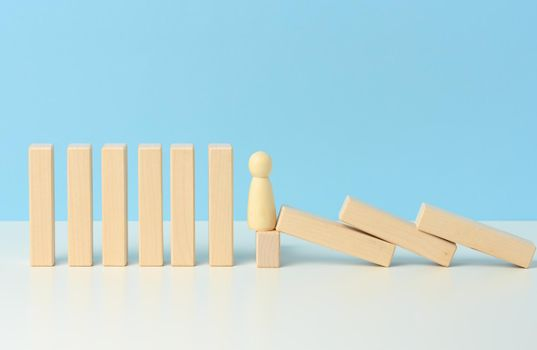 figures of men restrain the falling of wooden blocks, the effect of dominoes on a blue background. concept of teamwork