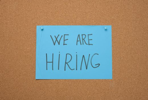 blue sheet of paper with an inscription on a brown cork board. Recruitment concept, vacancy