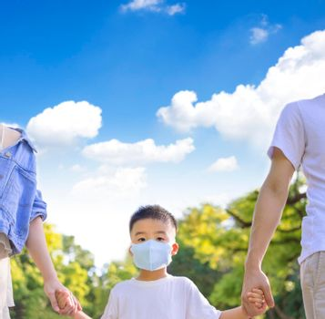Boy wearing the medical mask and walking parent in the park.