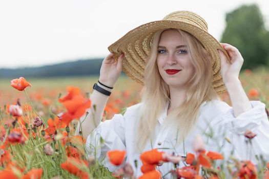 Attractive young woman holding straw hat poppy field.
