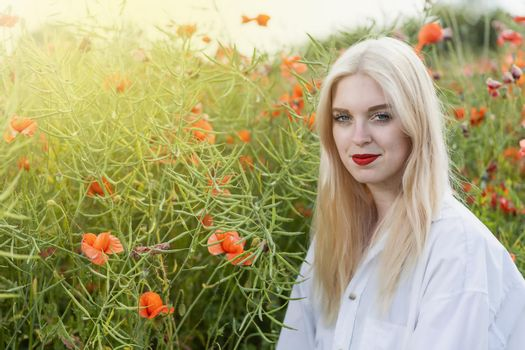 Blonde oung woman posing in red poppy field.