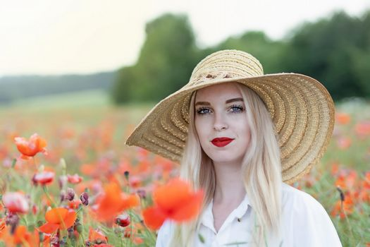 Attractive young woman is posing in red poppy field.