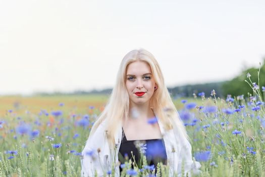Front view portrait of attractive woman posing in summer meadow