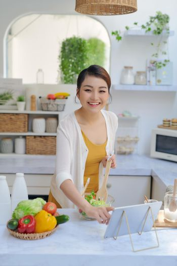 Woman cooking according the tutorial of online virtual master class,